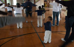 The rain kept the kids at the Stewpot after-school program indoors yesterday. Kindergartener Damante gets his daily excercise in the gym among Harvard student volunteers. Photo: Diane Ghogomu