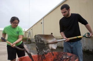 From left, Alternative Spring Break volunteers Geetika Mehra, '12 and Seth Pearce '12 shovel mud while cleaning up the parking lot The Humane Society in Gulfport, Mississippi. Staff Photo: Kris Snibbe/Harvard News Office
